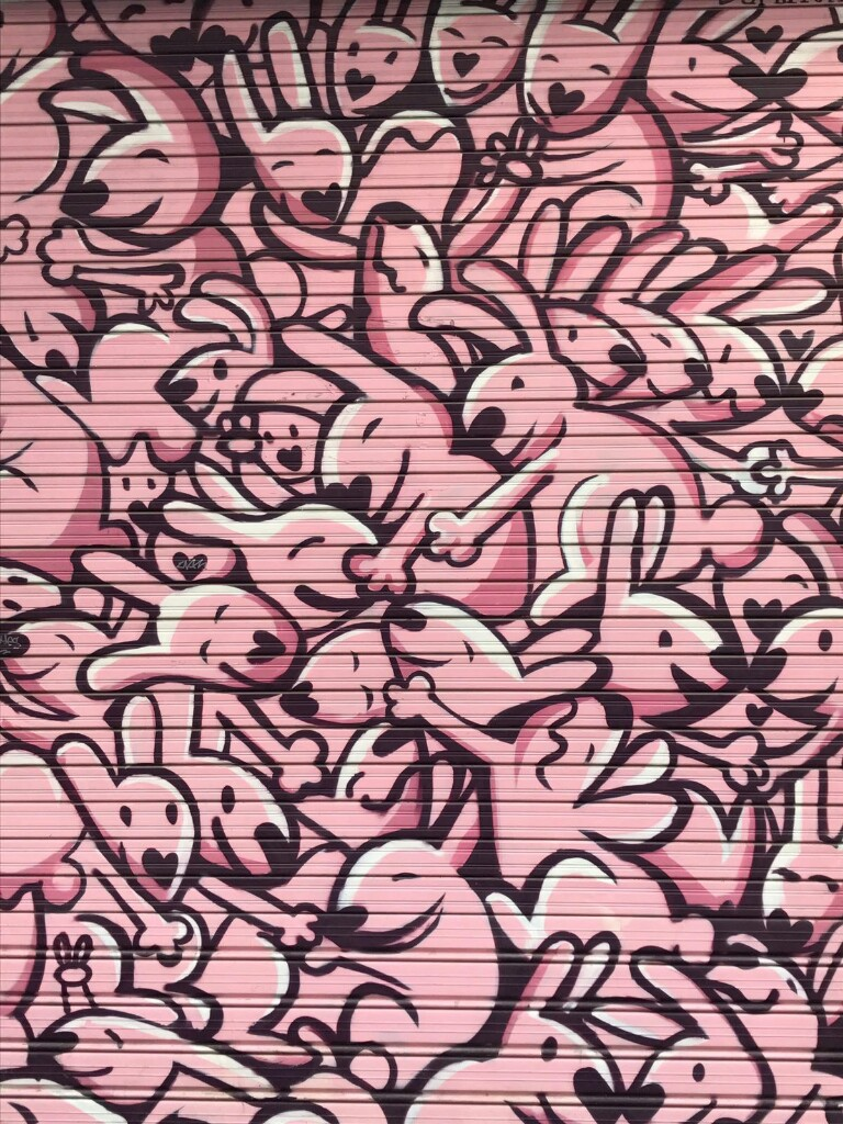 Mural of a crowd of pink rabbits all hugging each other