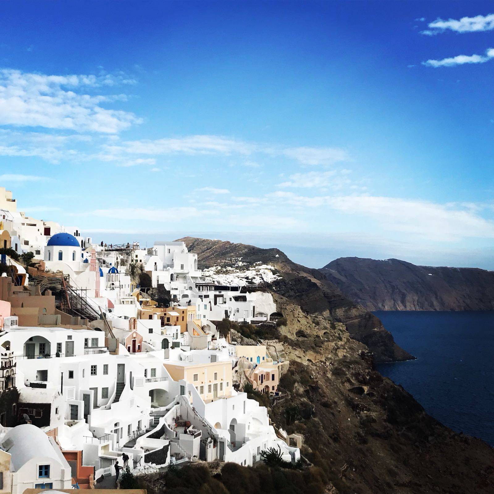 The houses of Oia, viewed from the side, showing the different coloured houses running down the cliff