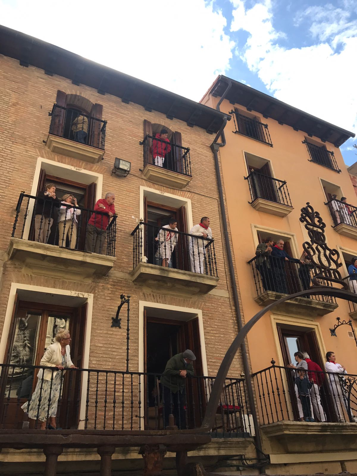 The balconies of two buildings on the bull run filled with all ages of locals watching