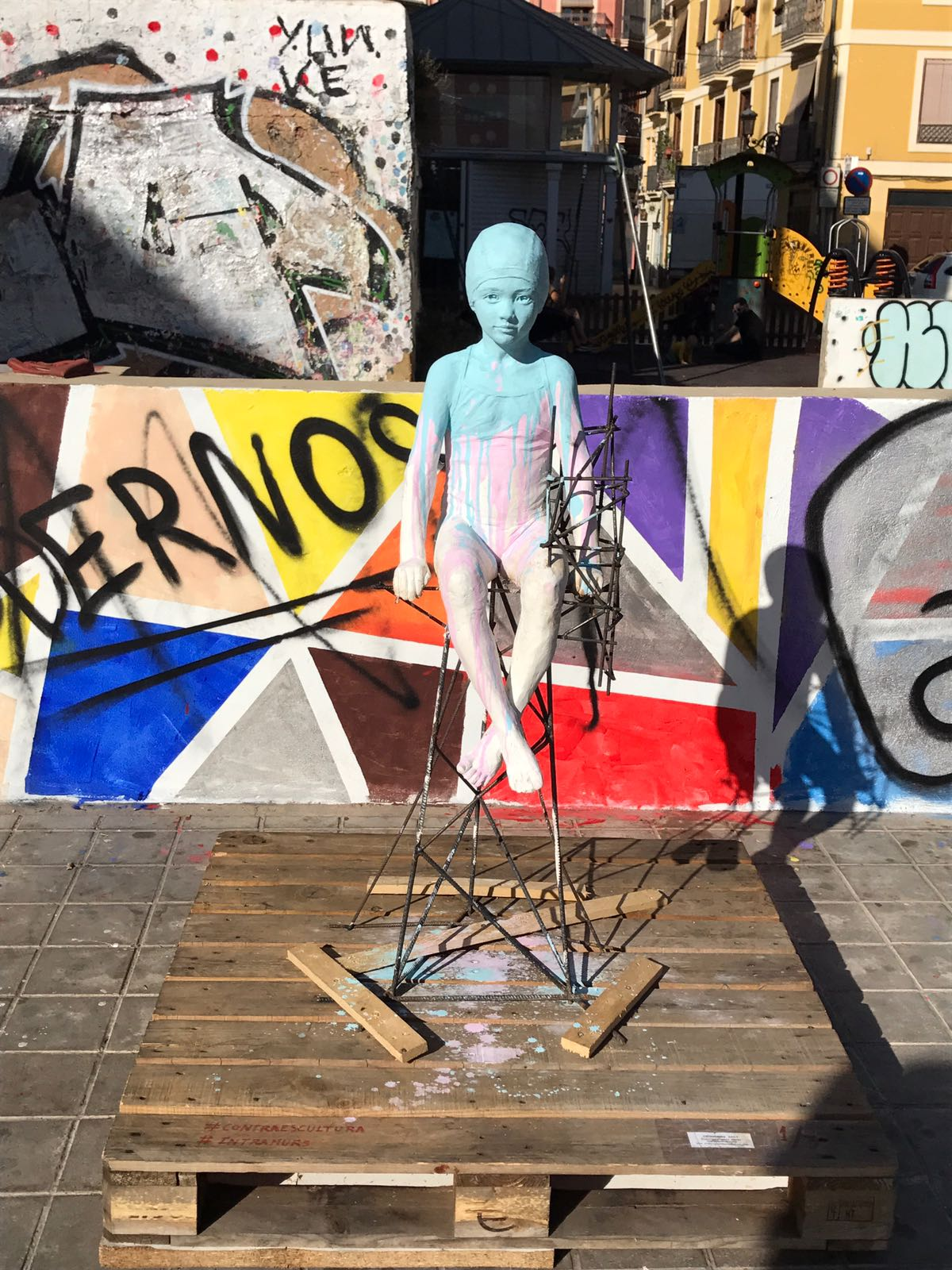 Sculpture of girl made in plaster, splashed with paint sitting on a wire chair on a wooden pallet