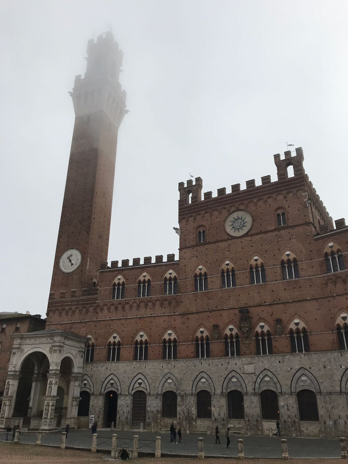 Palazzo del Pubblico with a grey misty background and the top of its tower lost in the mist