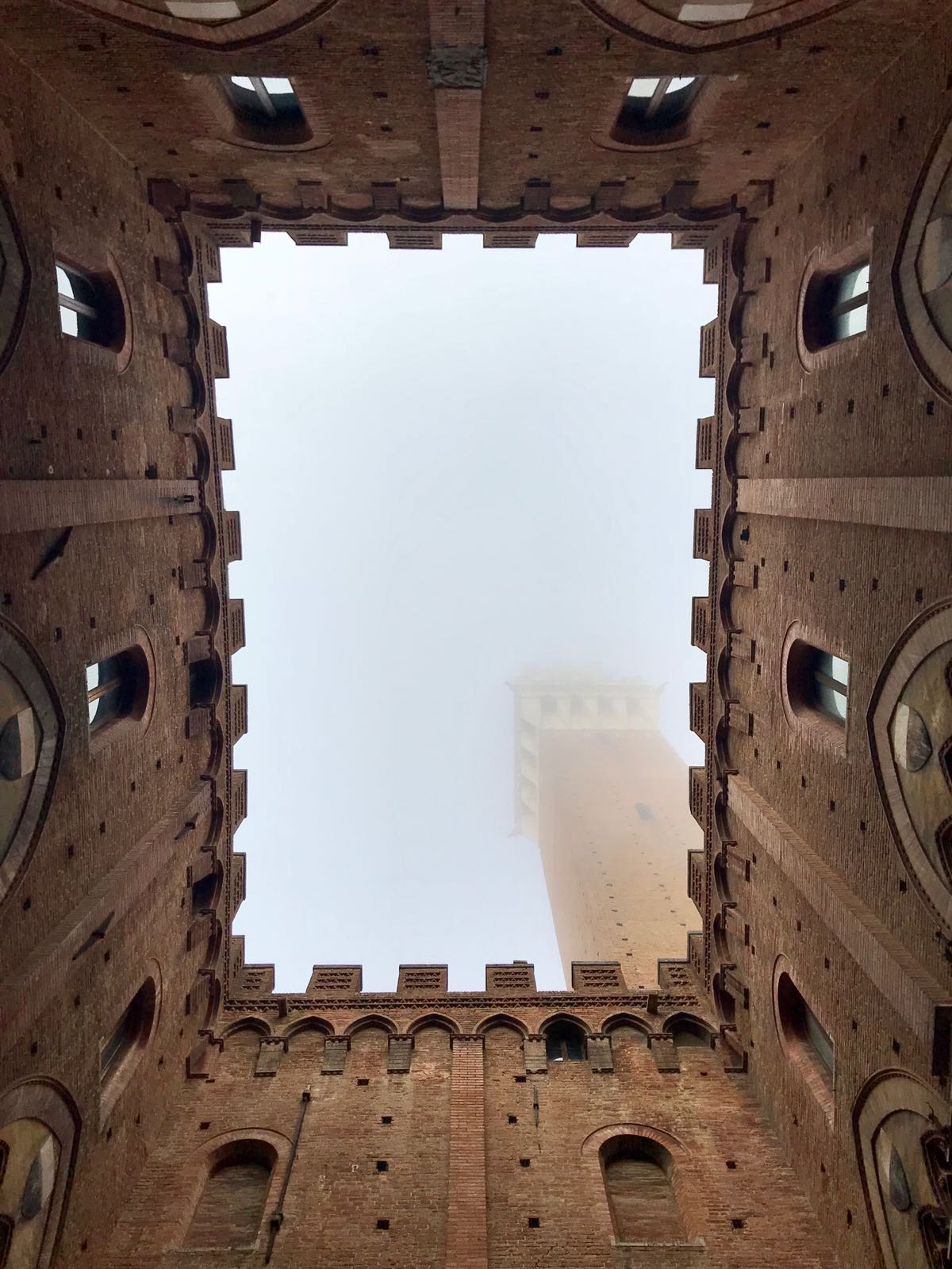 View of the Palazzo del Pubblico tower disappearing into the mist from its internal courtyard