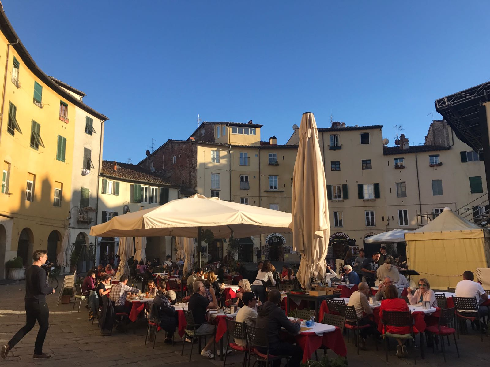 Many people dining under a blue sky in the centre of the Piazza Anfiteatro in Lucca