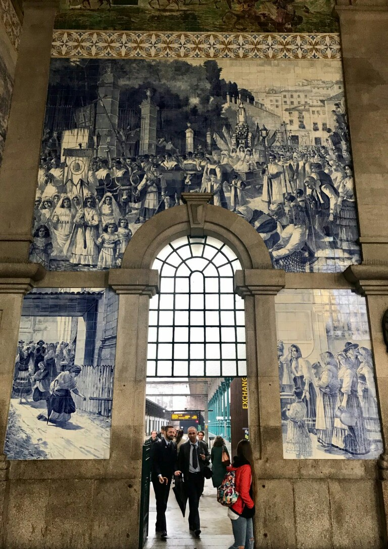 Arch in Porto station surrounded by decorative tiles depicting scenes from Porto's history