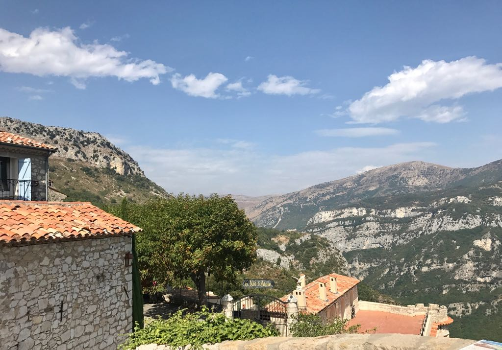 View over the rooftops of Gourdon, showing the mountains ahead and the valley below
