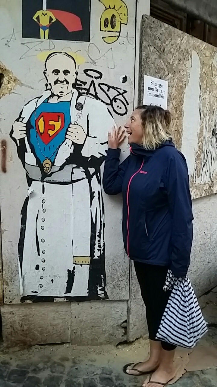 Roz staring in awe at some graffiti of the current Pope opening his shirt to reveal a superman costume