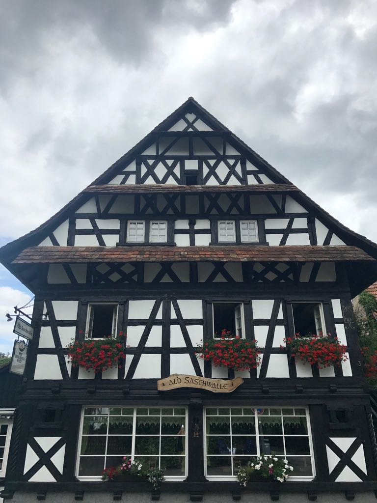 sasbachwalden timber house with window boxes filled with red flowers