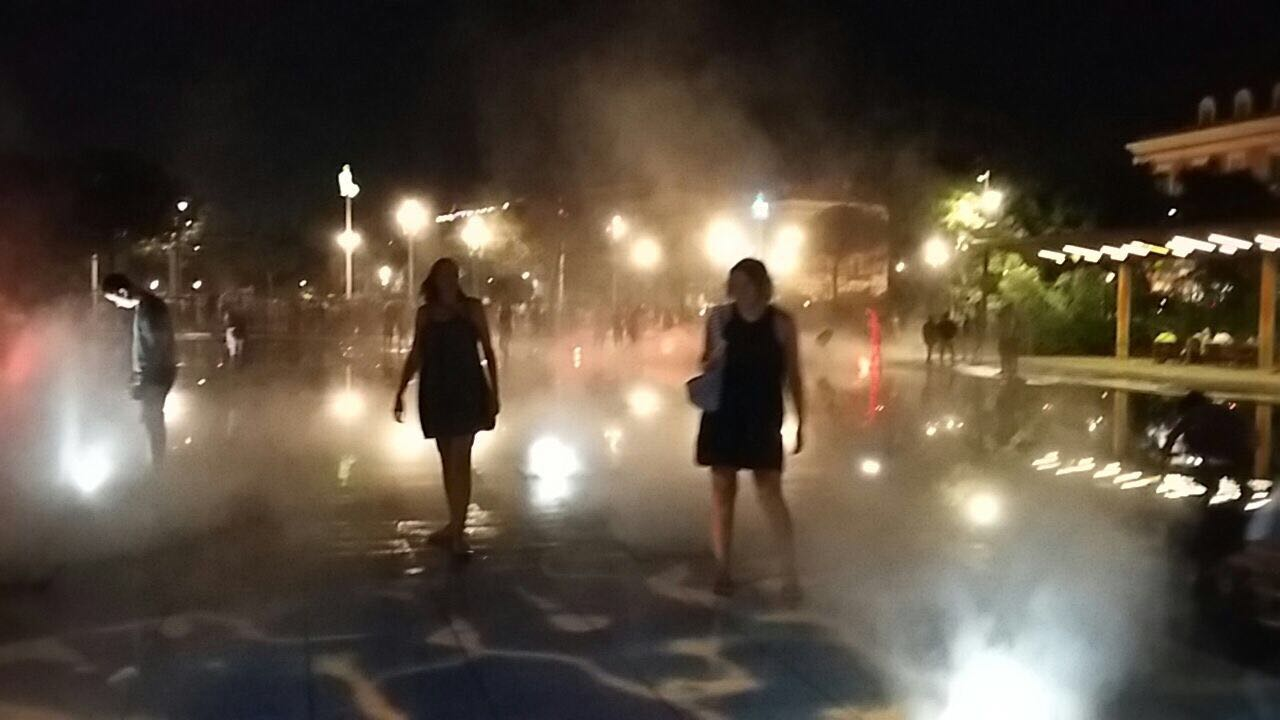 Roz and Siân in surrounded by mist and different colours from a fountain in Nice