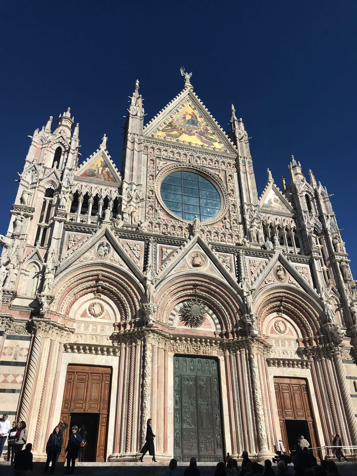 Siena Cathedral facade in the sunshine with the wood and bronze doors at the front