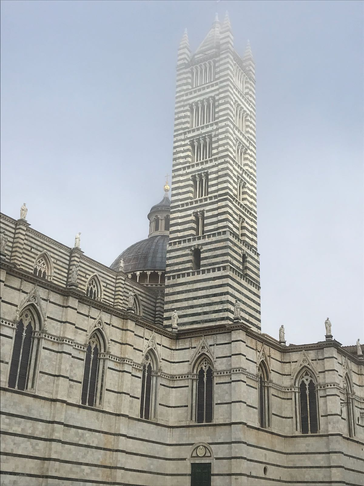 Siena Cathedral tower with the top disappearing into the mist
