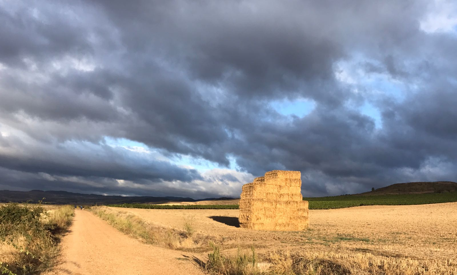 A stack of hay bales, lit yellow by the sun under a dark sky