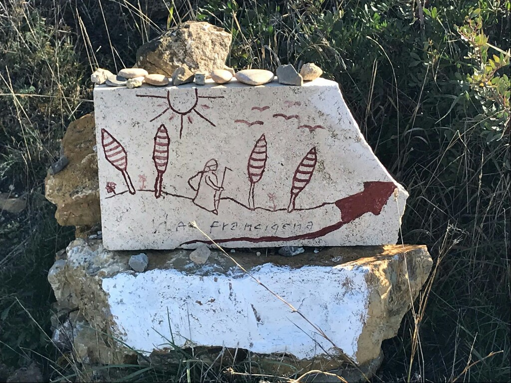 Francigena stone marker with a cartoon of a pilgrim walking a path lined with cypress trees