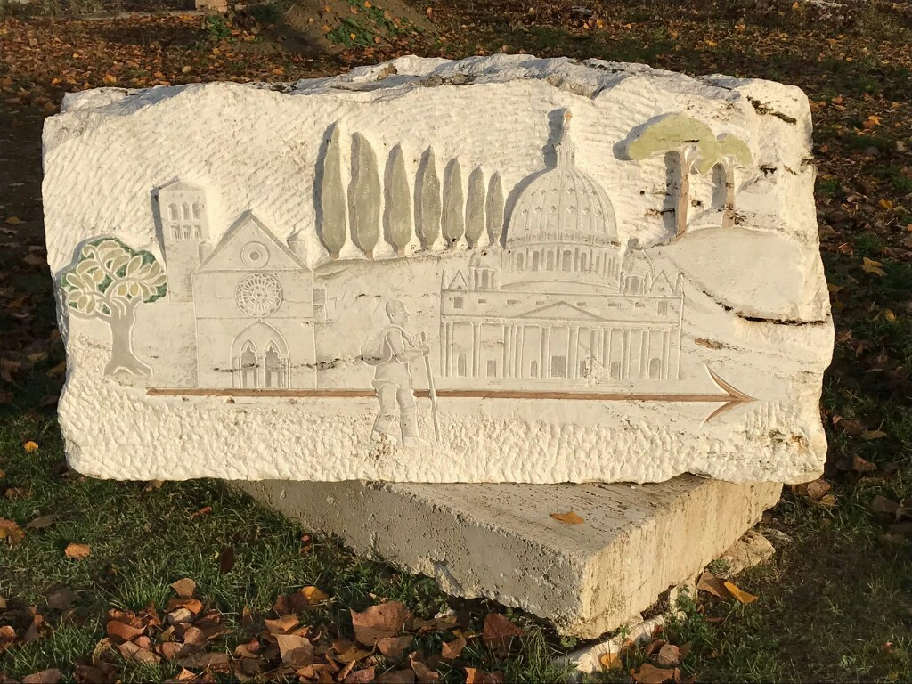 Francigena stone marker with picture of a pilgrim walking with various landmarks in the background like st Peters basilica