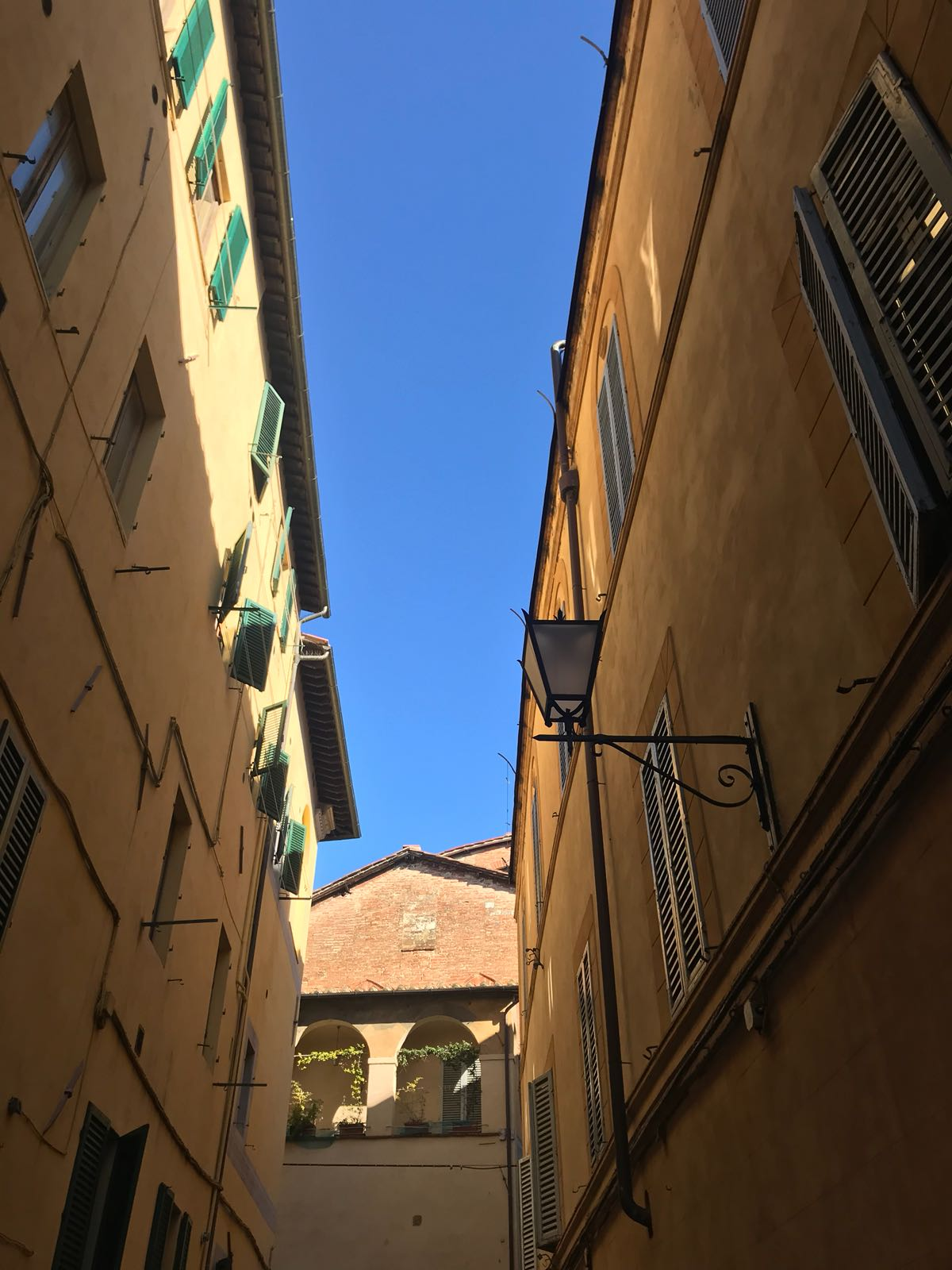 Blue sky, framed by a street in Siena also showing one of the local streetlights