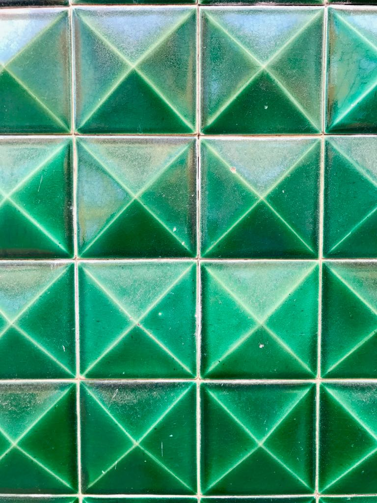 Wall of green tiles, each pointing outwards in a pyramid shape