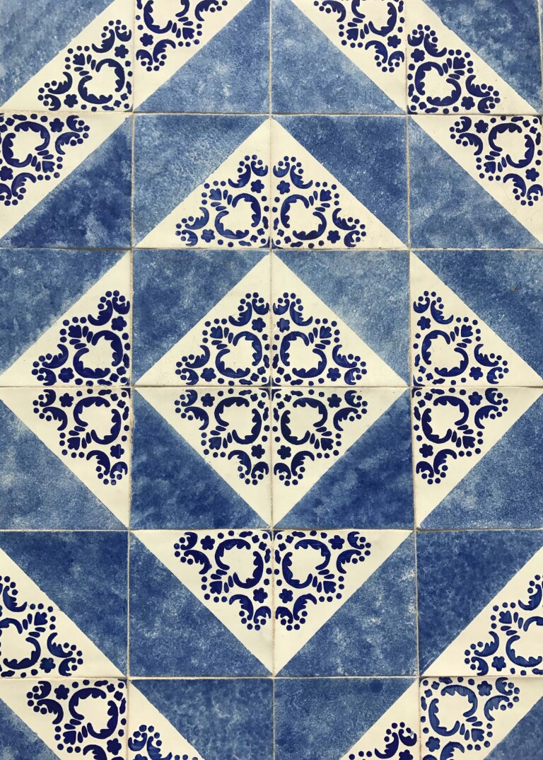 Tiles split into white and blue diagonally with dark blue patterns on the white section