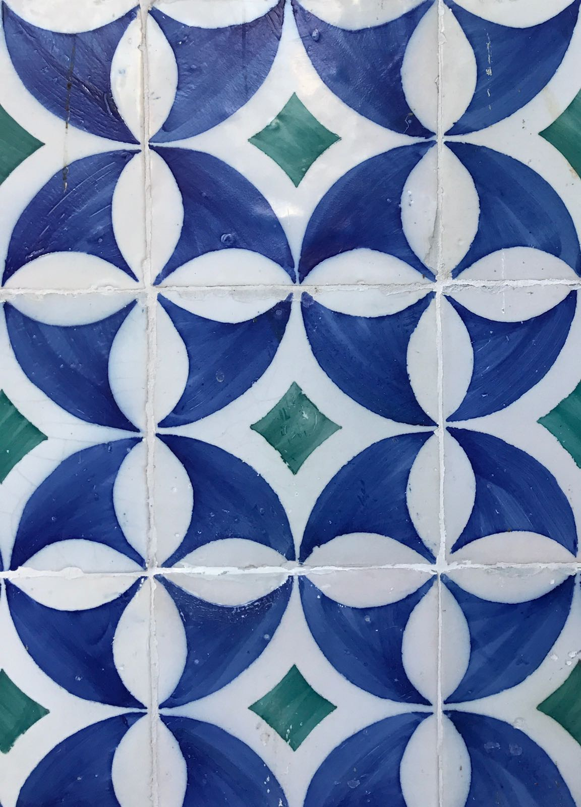 Wall of tiles which together form circles of white and blue on green