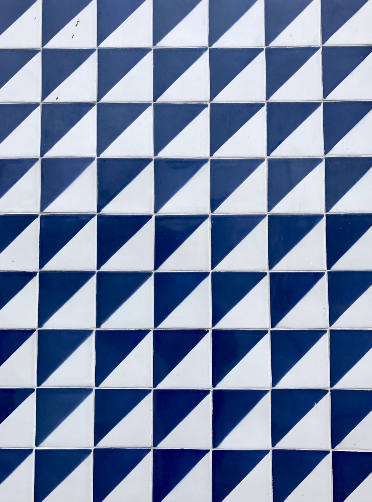 Wall of tiles split diagonally into blue and white sections