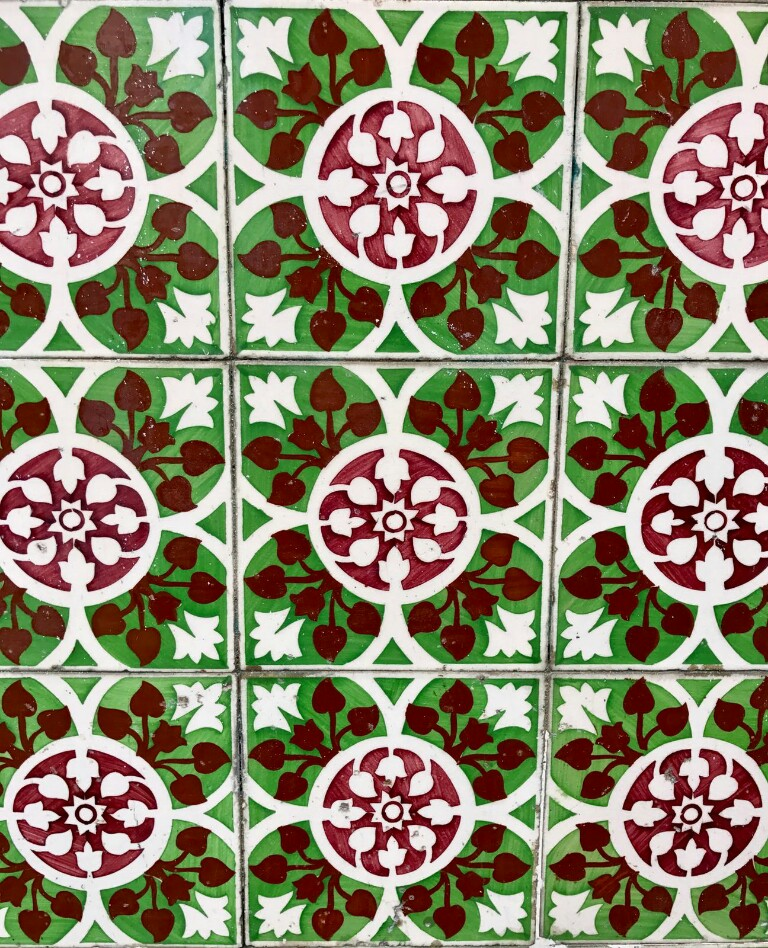 Green tiles with a centralised white pattern with some parts filled in with brown