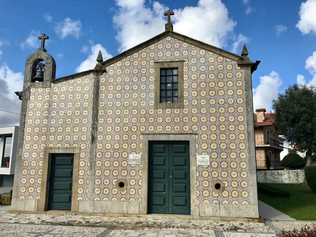The side of a small church chapel tiled with a repeated pattern of yellow circles