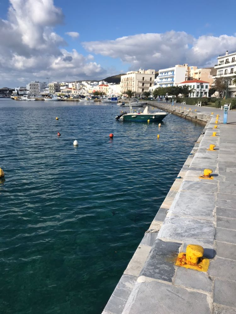 Tinos town harbour from the dock showing the local boats and the clear water