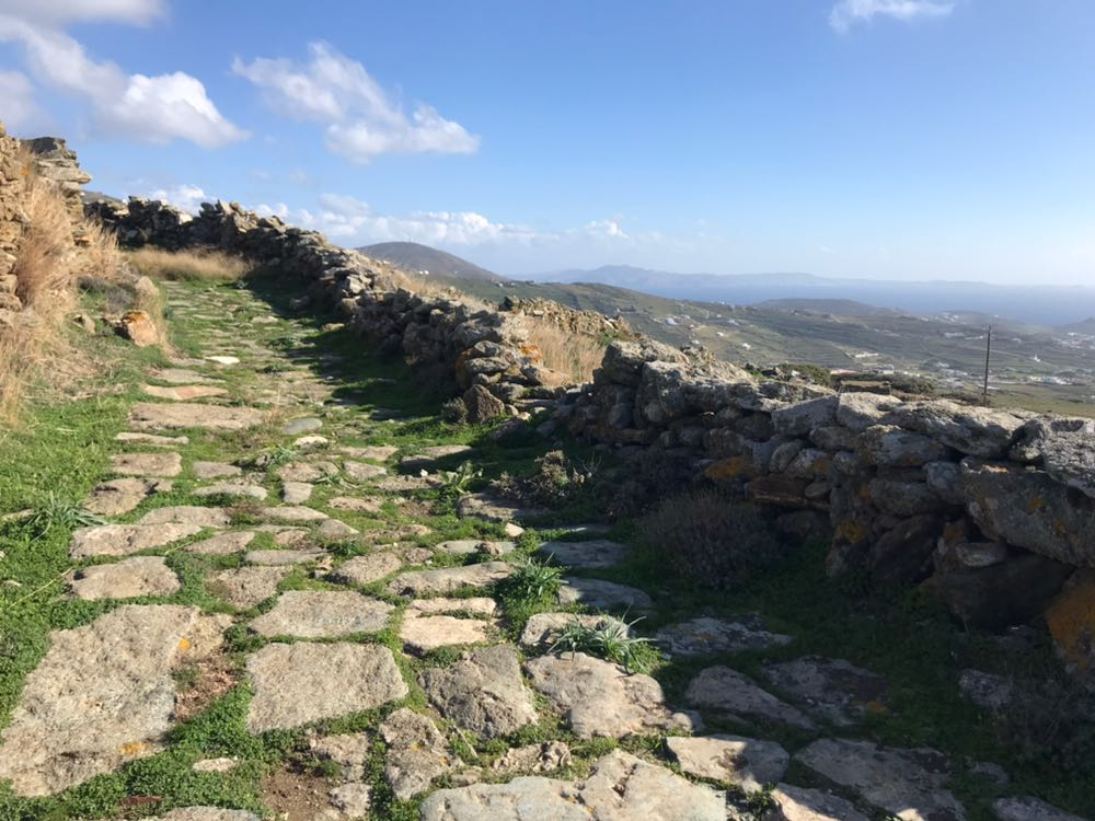 A walking path along the flat of a stepped hill, looking out across Tinos