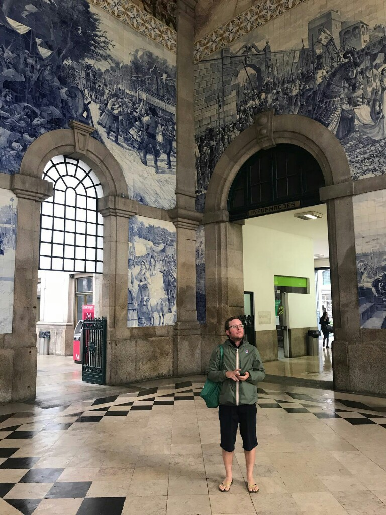 Tom in Porto station surrounded by ceramic tiling