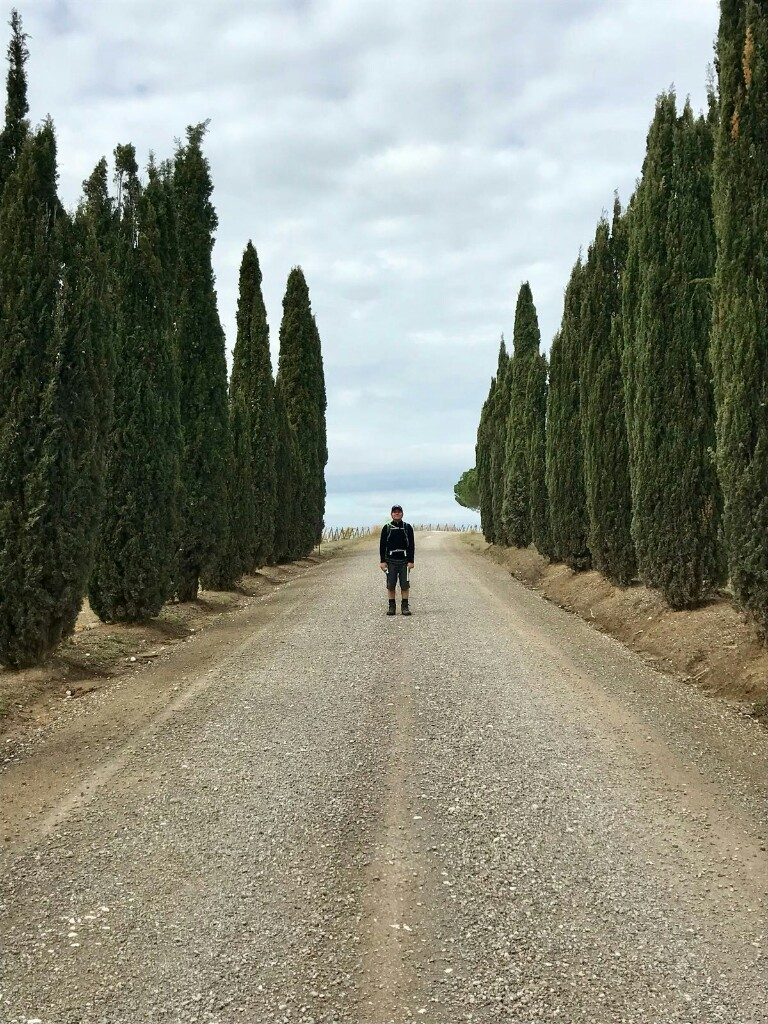 Tom on a path lined with cypress trees