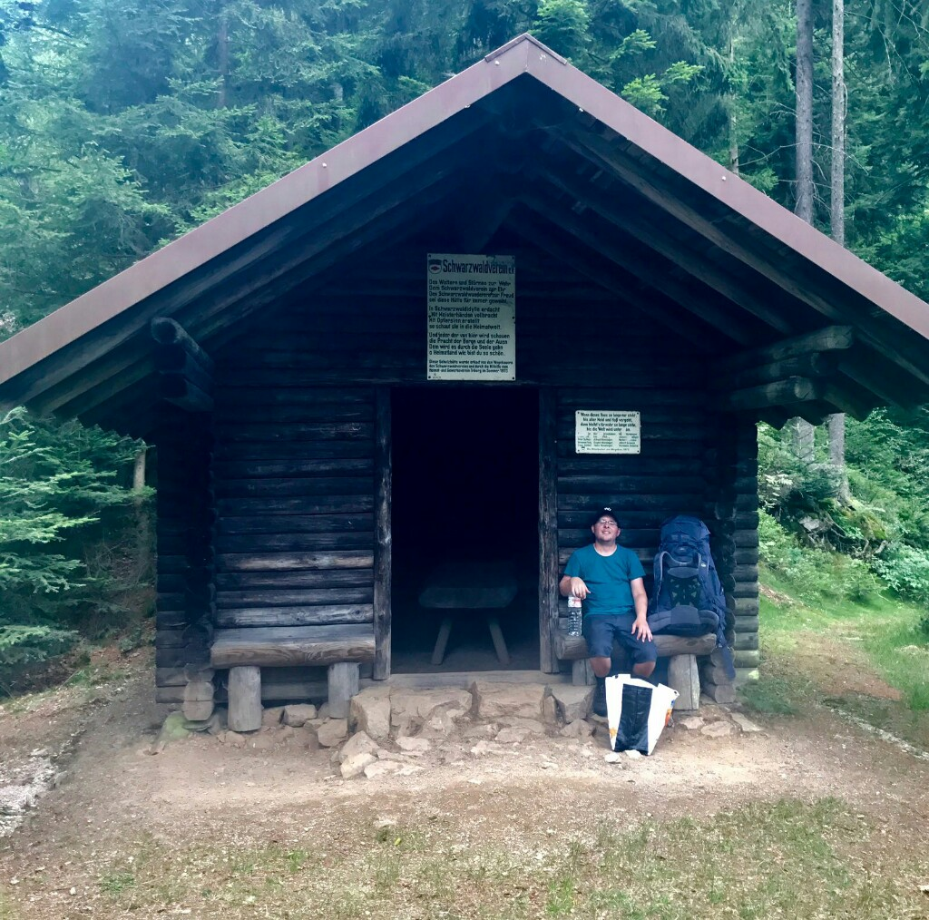 tom on a bench outside a wooden hut in the forest