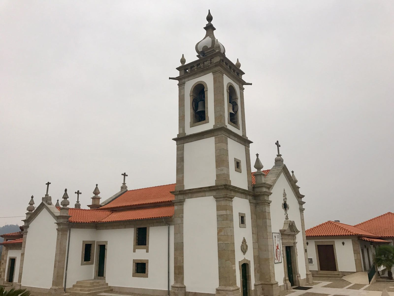 A Portuguese church with white walls, a red tile roof and a spire like the dome of a minaret