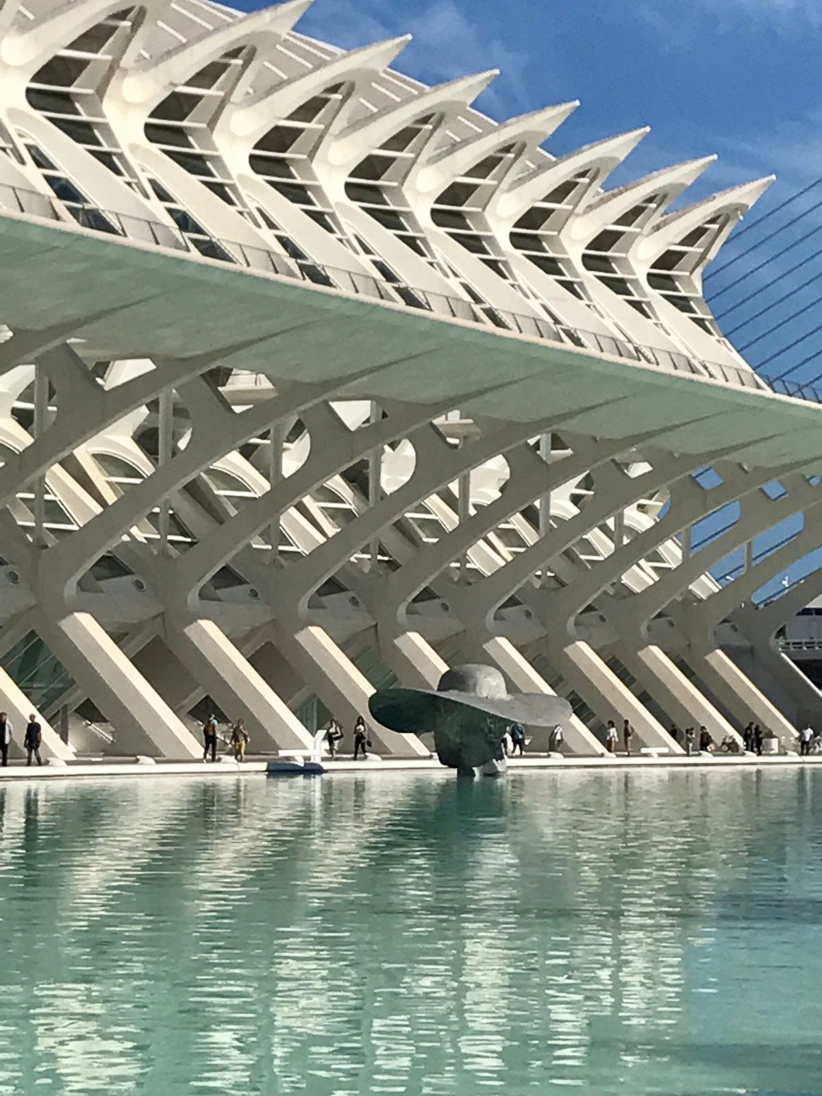 Spikey side of the Valencia science museum with a metal sculpture in the pool in front of a lady with a big hat