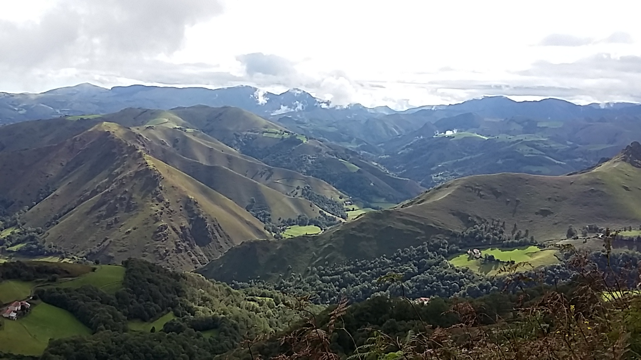 View from the Pyrenees mountains with clouds hovering over hills in the valley