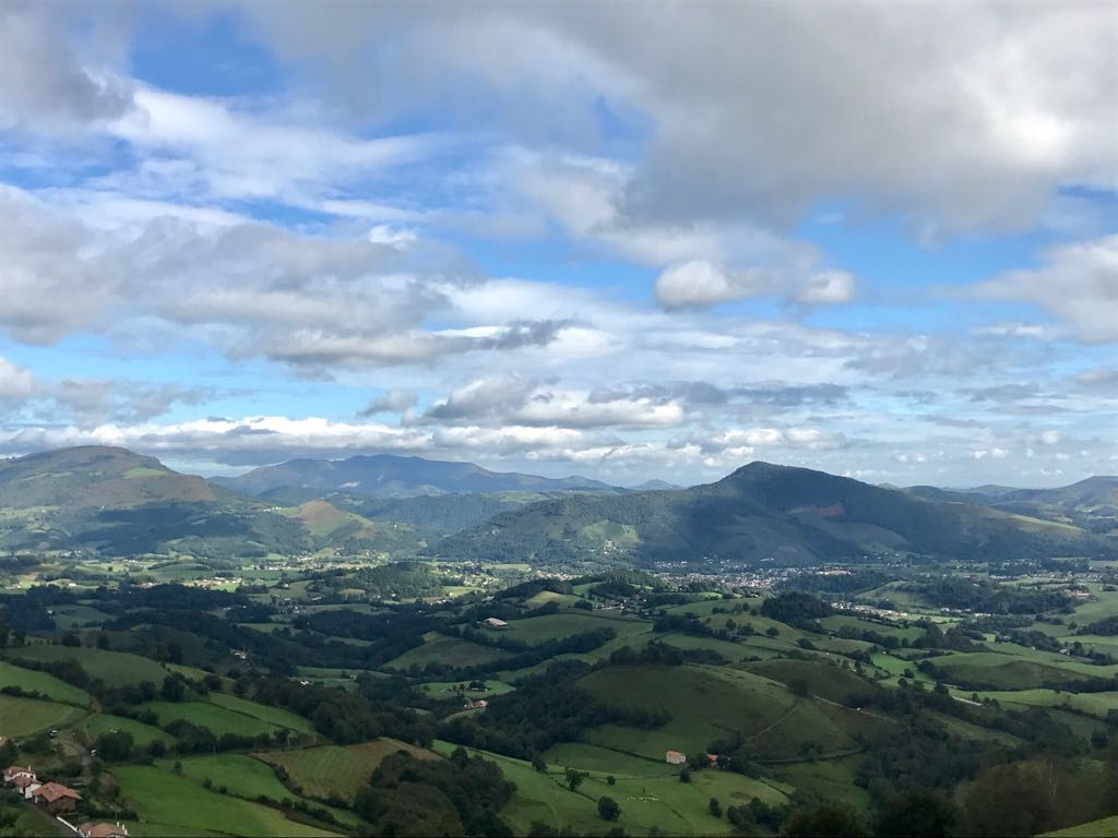 View from the Pyrenees mountains with clouds casting shadows on fields in the valley