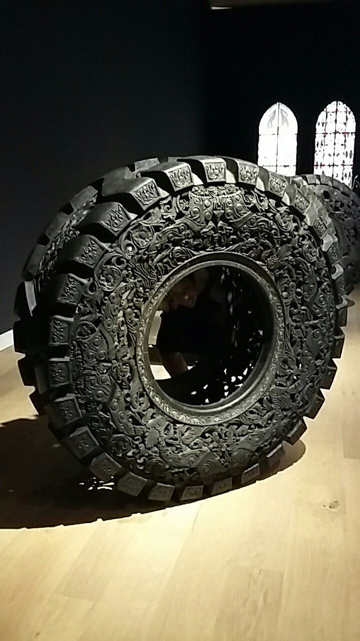 Wim Delvoye work looking like a truck tyre engraved with complex patterns you'd normally see in church ironwork