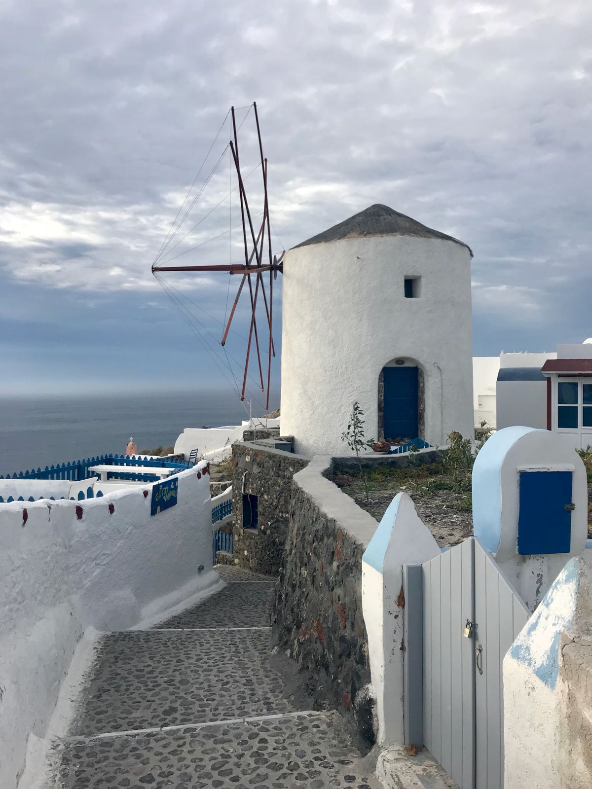 Windmill in Oia nested between houses, on the edge of a path between them