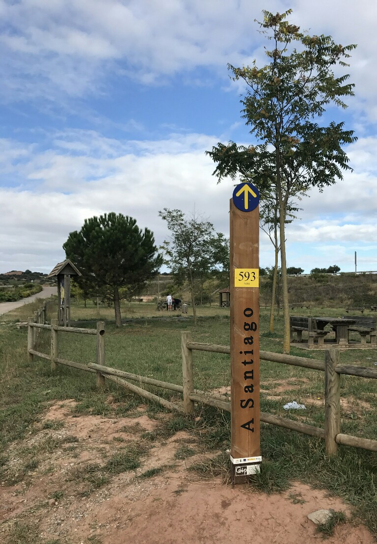 wooden pole showing the distance to santiago