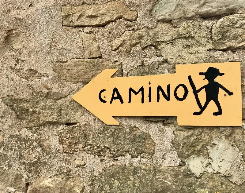 yellow arrow sign with silhouette of smoking pilgrim