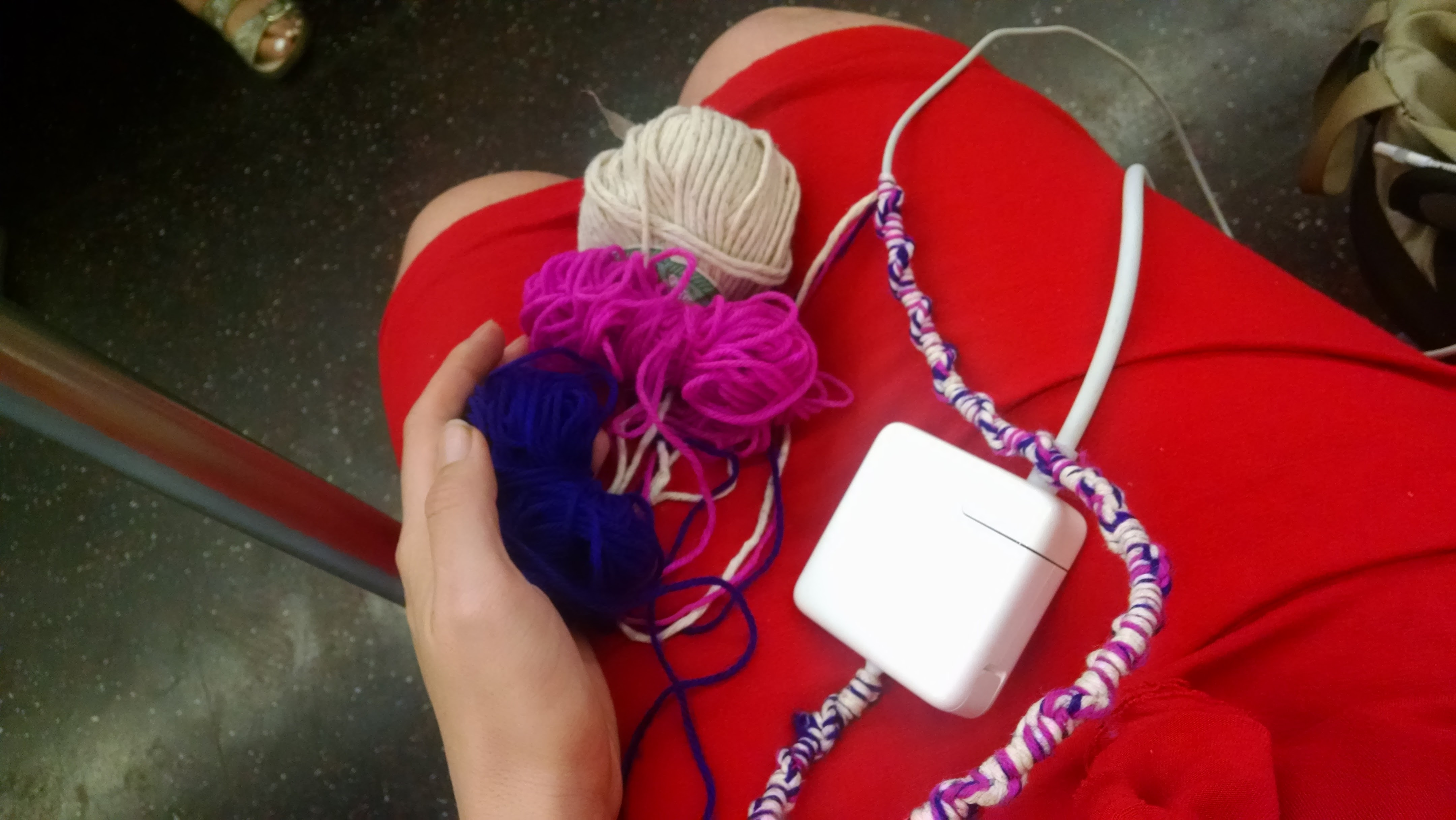 partly covered charger and balled yarn across my lap while I sit on the subway
