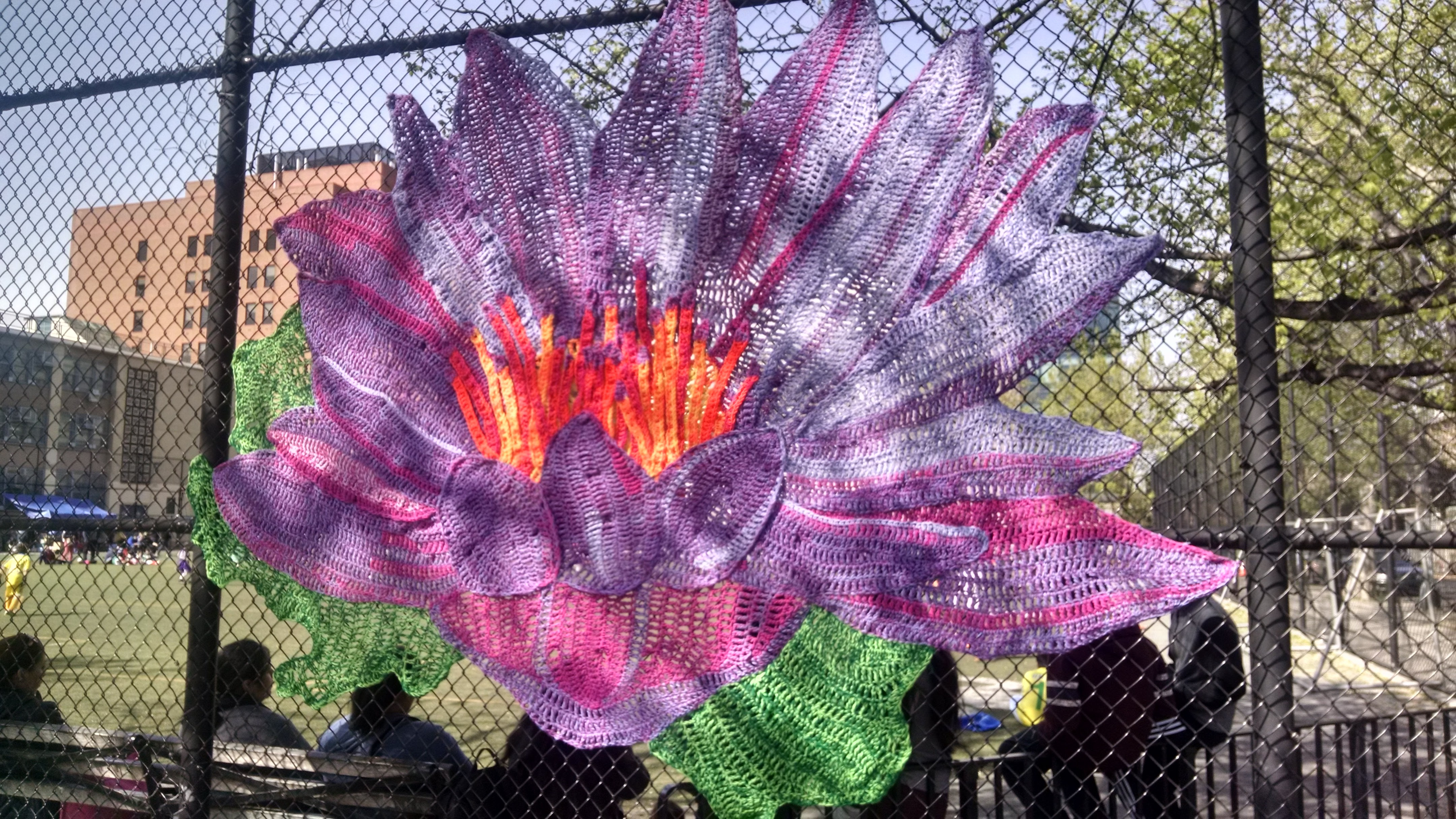 yarn weaved into chain link fence to make a large flower of pink and purple